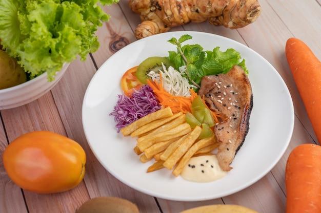 Posta de peixe com batatas fritas, kiwi, alface, cenoura, tomate e repolho em um prato branco.