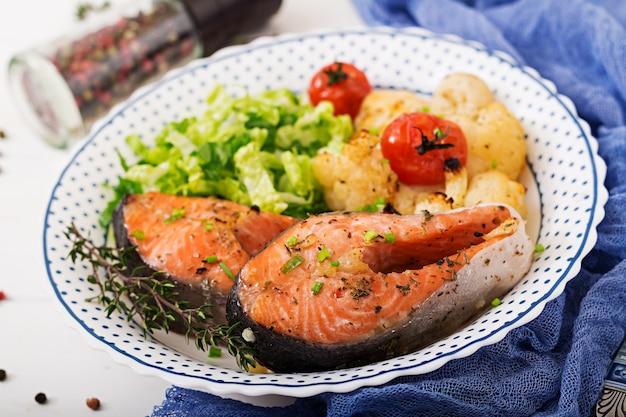 Posta de salmão assada com couve-flor, tomate e ervas. nutrição apropriada.