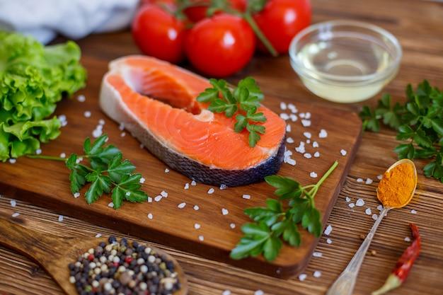 Posta de salmão com legumes e especiarias em um espaço de madeira. o conceito de cozinhar. espaço de supermercado.