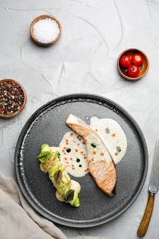 Posta de salmão com molho no prato de cerâmica. salmão assado com rolo de abobrinha e ingredientes na mesa de concreto
