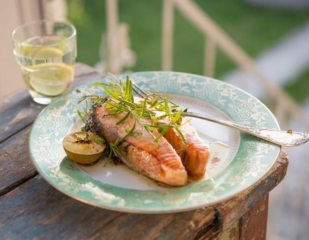 Posta de salmão grelhada com copo de água, ceia. comida saudável. vista do topo