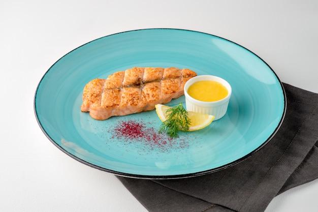 Posta de salmão grelhada com limão e molho no prato colorido e guardanapo em fundo branco