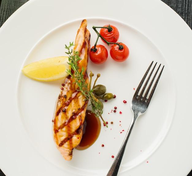 Posta de salmão grelhada com limão e tomate cereja. vista de cima