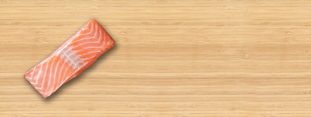 Posta de salmão isolada no fundo da placa de madeira. vista do topo. banner horizontal