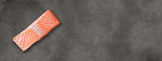 Posta de salmão isolada no fundo escuro do tabuleiro de concreto. vista do topo. banner horizontal
