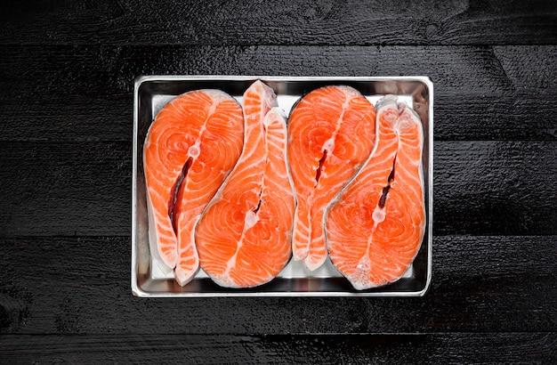 Posta de salmão na vista superior de mesa de madeira preta