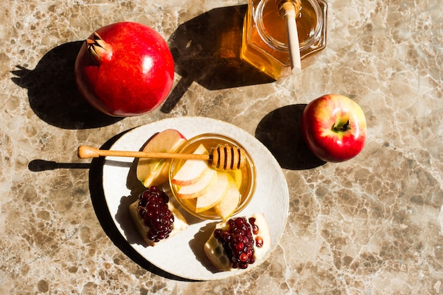 Postal concept rosh hashanah com maçãs, romãs e mel em fundo de mármore