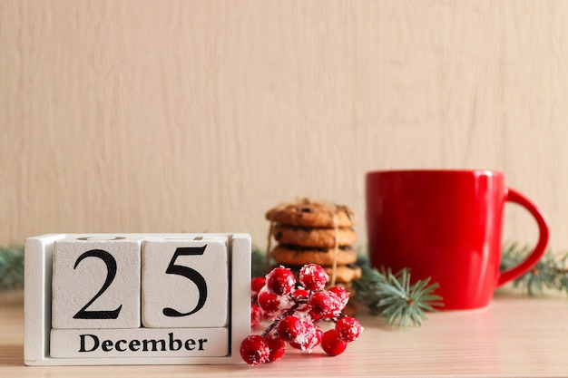 Postal de natal com biscoitos no galho da árvore de cupfir de madeira, calendário datado de 25 de dezembro