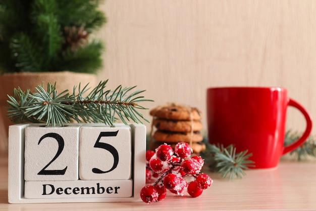 Postal de natal com biscoitos no suporte de madeira copo vermelho calendário de árvore de natal datado de 25 de dezembro