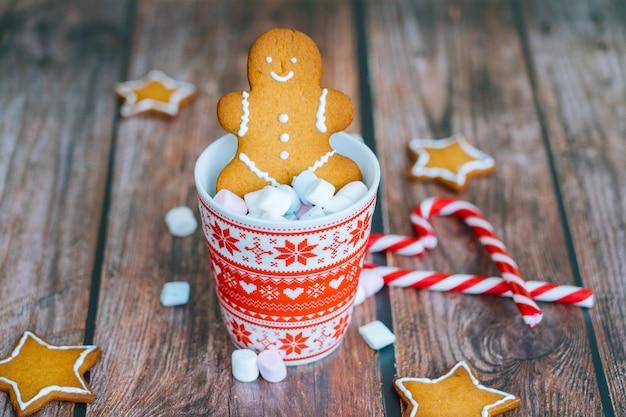 Postal de natal com caneca vermelha do homem-biscoito com enfeites de natal na luz bokeh da árvore de natal e doces listrados vermelhos de férias.