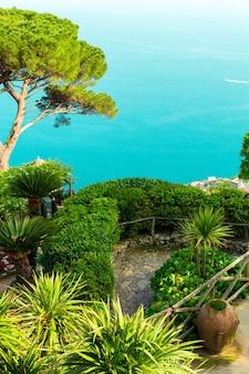 Postal fotográfico com terraço com flores e árvores, vasos de barro no jardim villas rufolo em ravello. costa amalfitana, campânia, itália