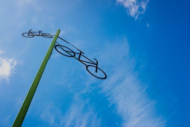 Poste com a figura de algumas bicicletas que indicam a estrada, com céu azul e nuvens no fundo.
