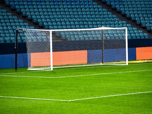 Poste da baliza branca na arena de jogo de futebol no fundo das fileiras de cadeiras vazias
