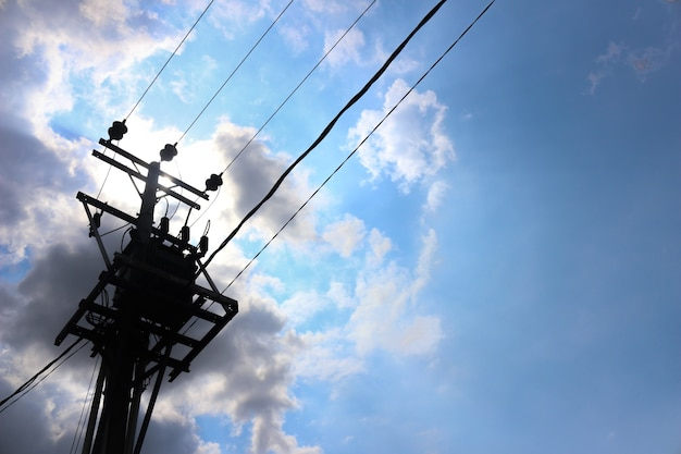 Poste de energia apoiando cabos de energia elétrica contra o céu azul