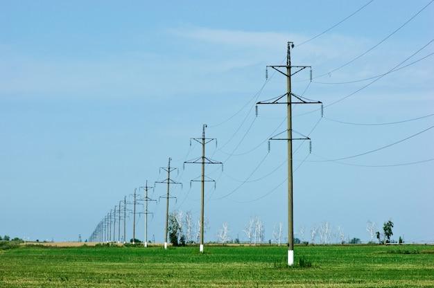 Poste de energia de alta tensão em campo verde