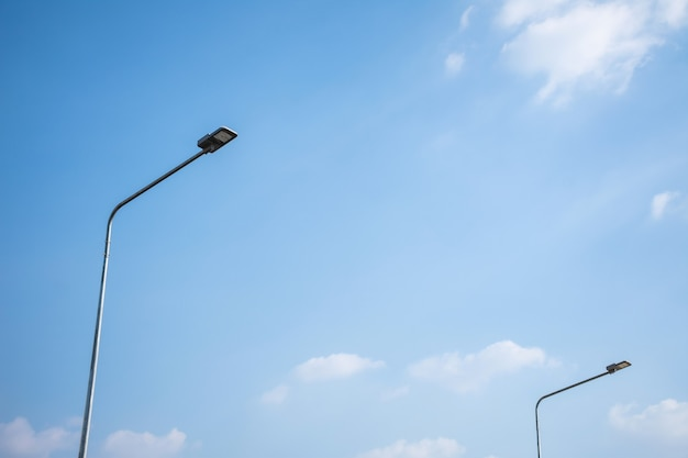 Poste de luz led em poste de aço com céu azul e nuvem.