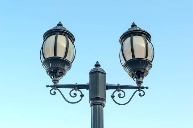 Poste de luz vintage contra céu azul