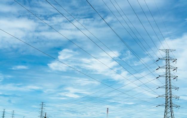 Poste elétrico de alta tensão e fio elétrico contra céu azul e nuvens brancas