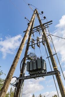 Poste elétrico na estrada com cabos de energia e transformadores