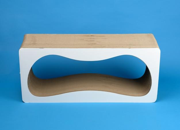 Poste para raspar papel feito de papelão ondulado em um fundo azul
