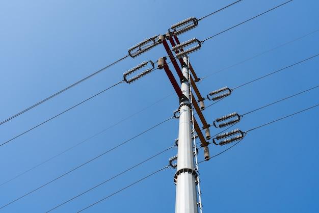 Poste telegráfico com cabos contra um céu nublado