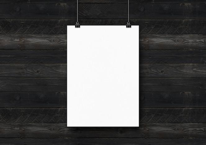 Pôster branco pendurado em uma parede de madeira preta com clipes