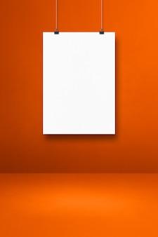 Pôster branco pendurado em uma parede laranja com clipes. modelo de maquete em branco