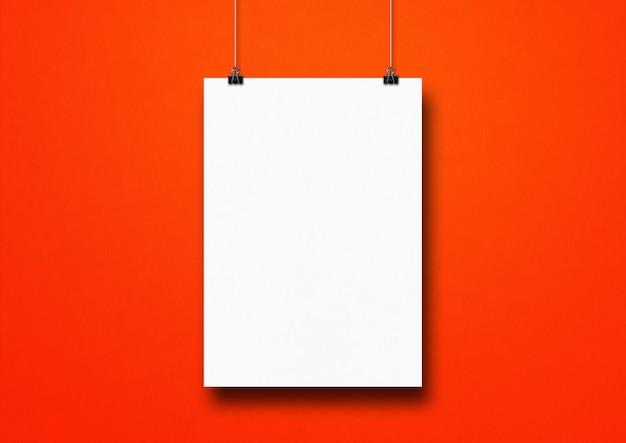 Pôster branco pendurado em uma parede vermelha com clipes. template em branco