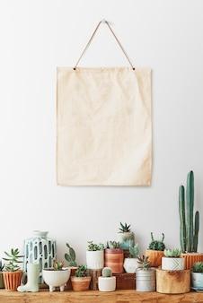 Pôster de tela em branco pendurado em uma prateleira cheia de cactos e suculentas