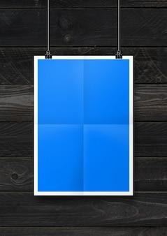 Pôster dobrado azul pendurado em uma parede de madeira preta com clipes. modelo de maquete em branco