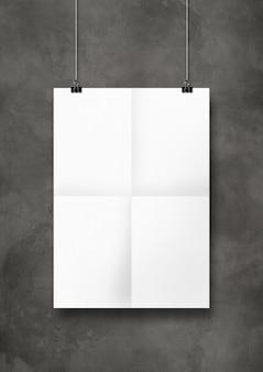 Pôster dobrado branco pendurado em uma parede de concreto com clipes