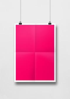 Pôster dobrado rosa pendurado em uma parede branca com clipes