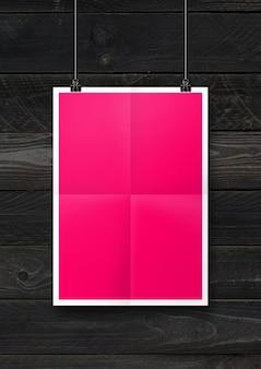 Pôster dobrado rosa pendurado em uma parede de madeira preta com clipes