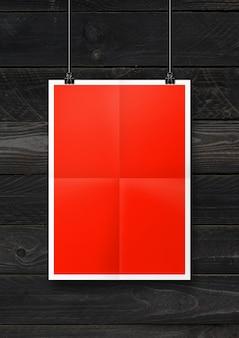 Pôster dobrado vermelho pendurado em uma parede de madeira preta com clipes
