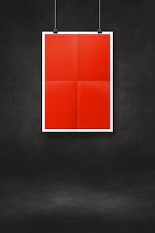 Pôster dobrado vermelho pendurado em uma parede preta com clipes. modelo de maquete em branco