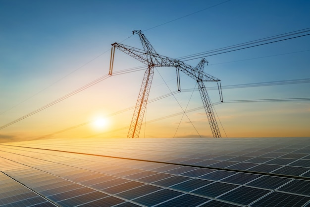Postes de alta tensão com linhas de energia elétrica transferindo eletricidade da energia solar fotovoltaica são vendidos ao nascer do sol. produção do conceito de energia sustentável.