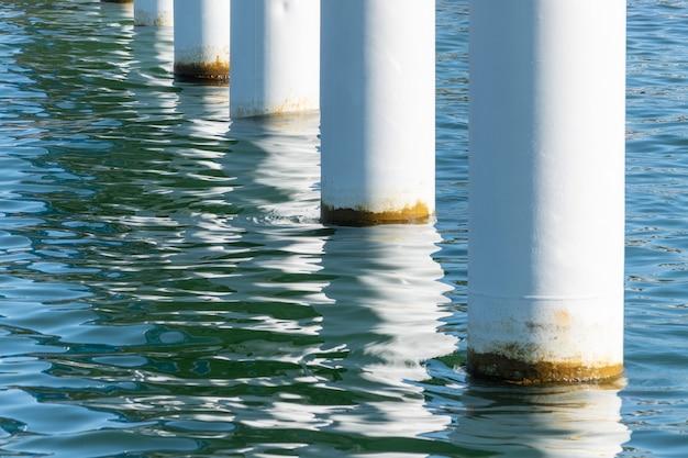 Postes de cais enferrujados na água do mar salgada. colunas brancas na diagonal. montagem de pilares para ponte. tempo ensolarado.