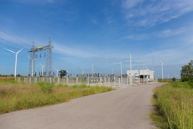 Postes de electricidade e usina ou estação com turbina de vento na natureza ao ar livre