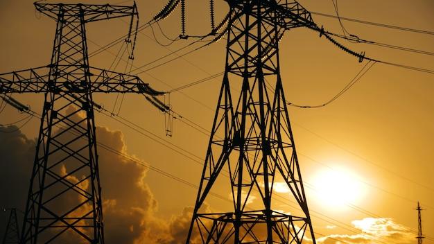 Postes de eletricidade e linhas de transmissão de energia elétrica contra um céu laranja vibrante na silhueta do pôr do sol ...