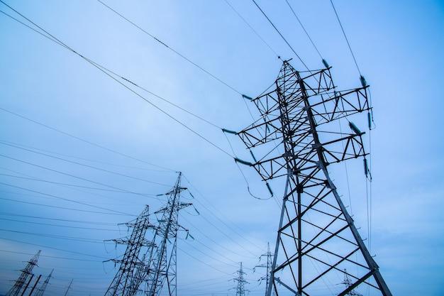 Postes de eletricidade no céu azul. força e energia.