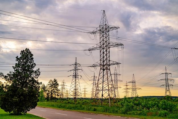Postes de eletricidade sustentando o fornecimento de energia em uma paisagem rural durante o pôr do sol. foco seletivo.