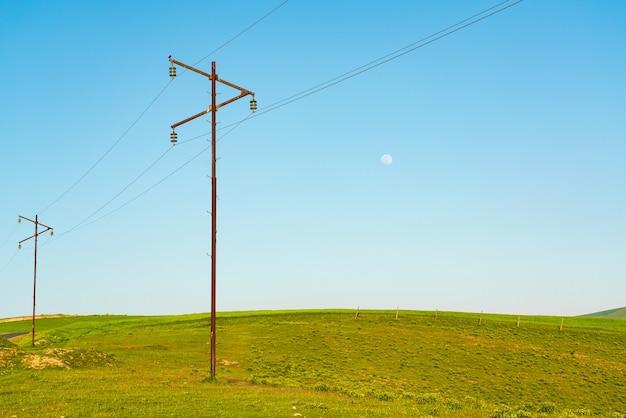 Postes de energia em um prado verde