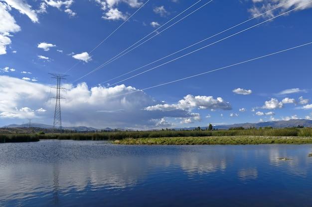 Postes de iluminação elétrica cruzando uma lagoa