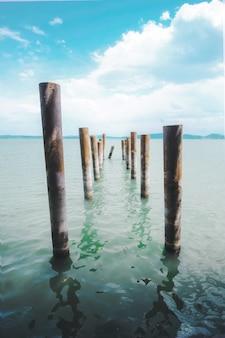 Postes de madeira marrons em corpo d'água durante o dia