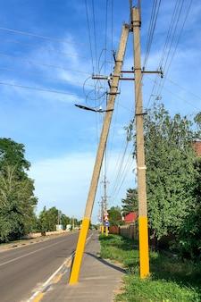 Postes elétricos ao longo da rua vazia da vila e céu azul no dia de verão