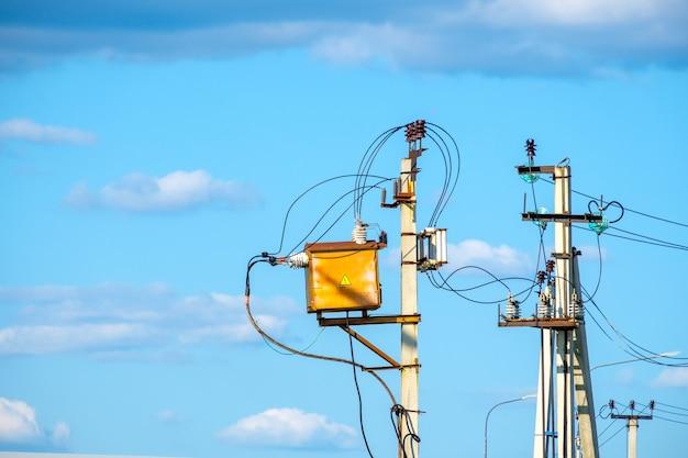 Postes elétricos com fios contra o céu azul