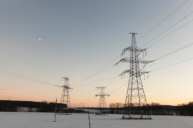 Postes elétricos fotografados na temporada de inverno. no chão há montes de neve após uma queda de neve. o céu ao fundo ao pôr do sol