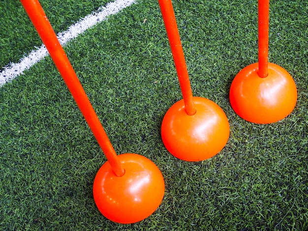 Postes laranja na grama verde no campo de futebol ou campo de futsal