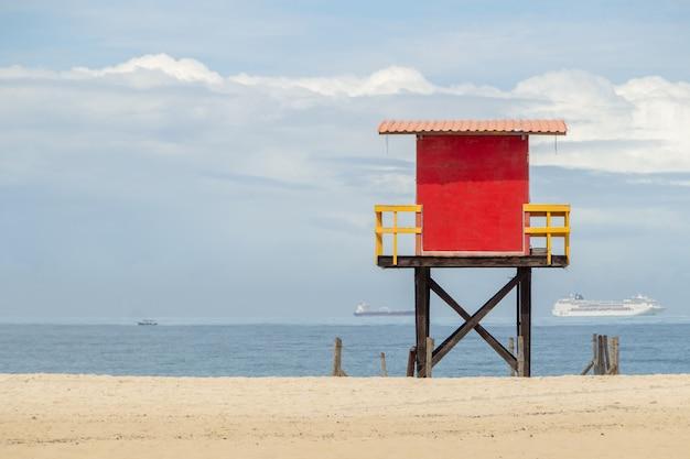 Posto vermelho do lifeguard na praia de copacabana com o mar e o céu azul em rio de janeiro.