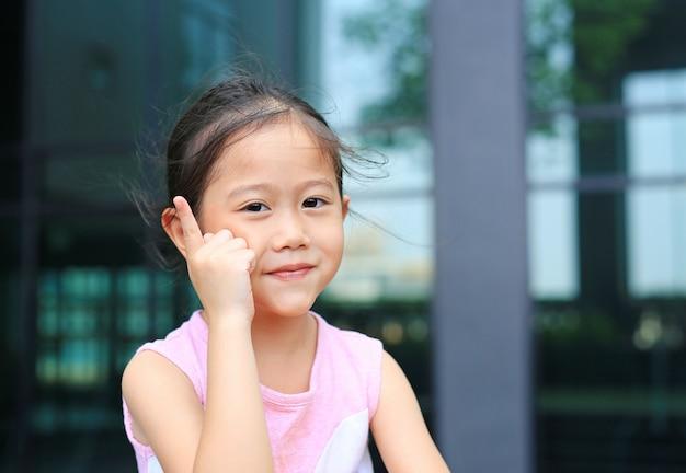 Postura asiática da menina que aponta seu dedo indicador acima com pouco sorriso.